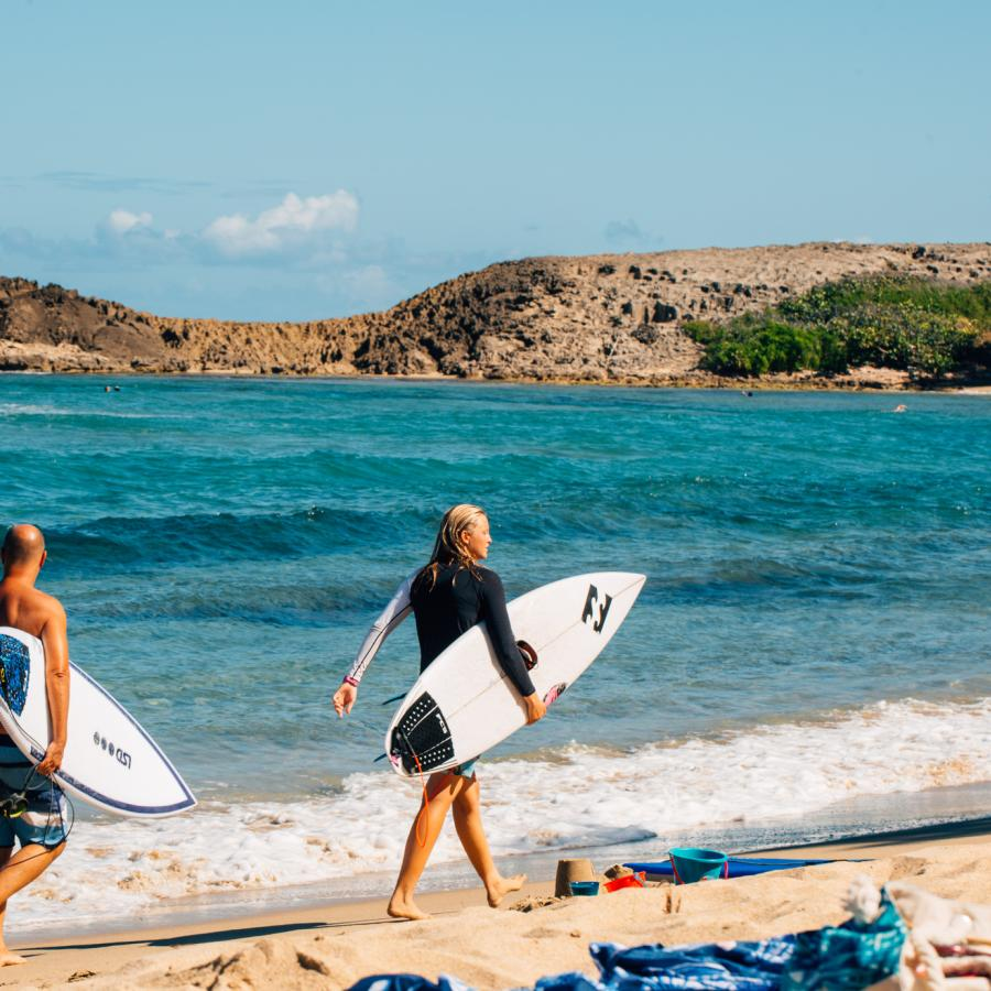 Two surfers stroll along Jobos Beach in Isabela, Puerto Rico.