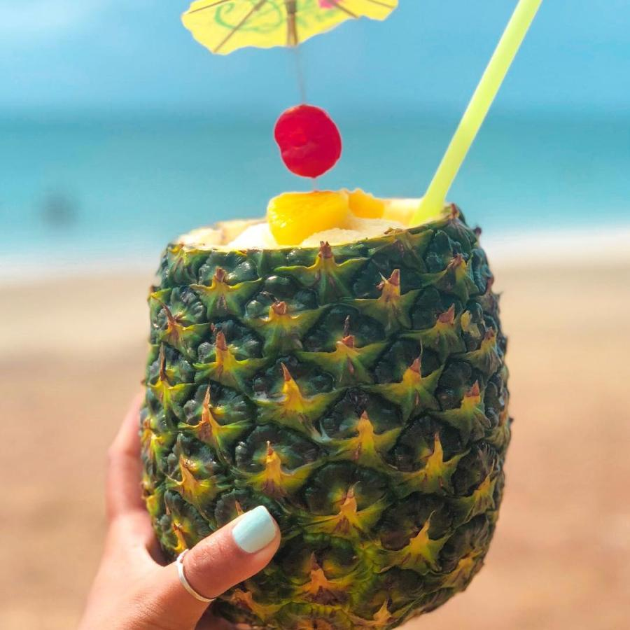 A hand holding a pineapple filled with piña colada.