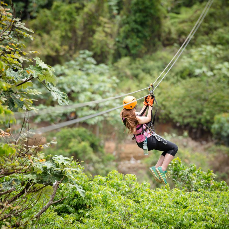 A woman ziplining over lush vegetation in Orocovis.