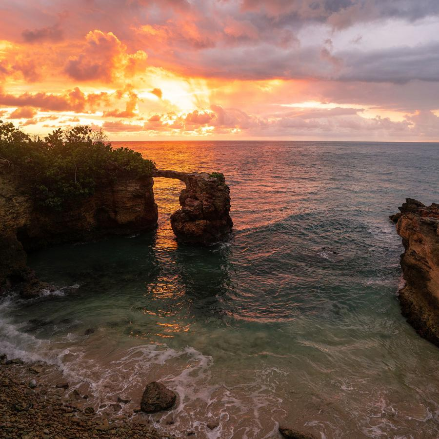 A dramatic sunset over the ocean with a beach surrounded by rock formations in the foreground