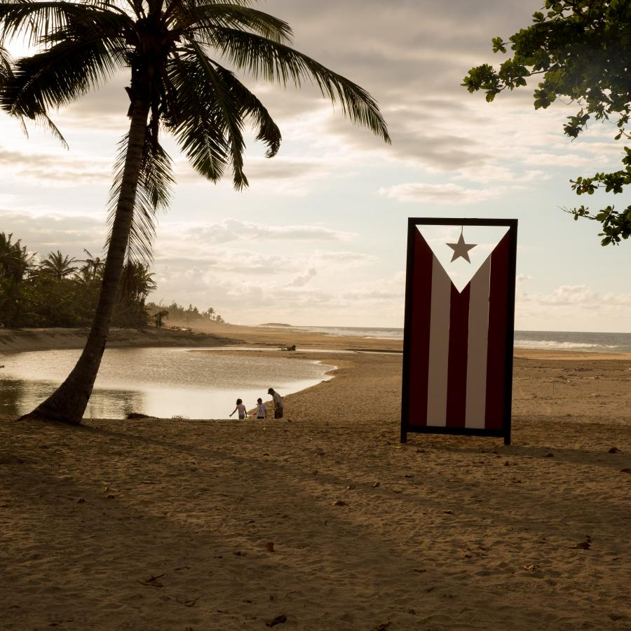 A sculpture of the Puerto Rican flag stands on a beach