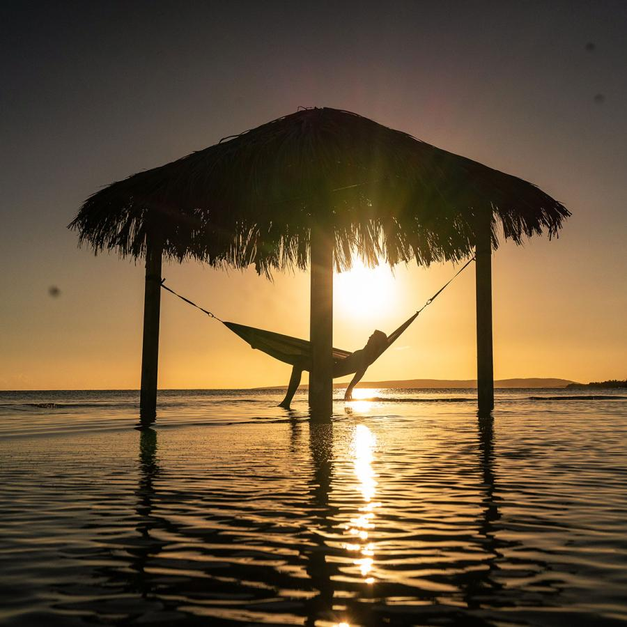 A person relaxes in a hammock as the sun sets in the background