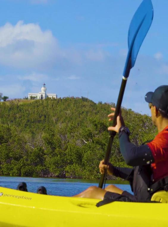 Kayaker paddling by Las Croabas Park and Fajardo's Lighthouse, the oldest lighthouse in Puerto Rico.