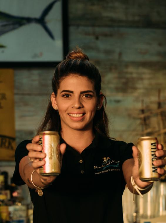 A bartender in San Juan holding two cans of Medalla.