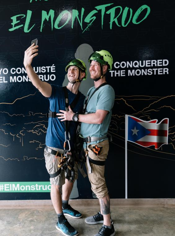"Two guys taking a selfie in front of ""The Monster"" sign at Toro Verde Zipline."