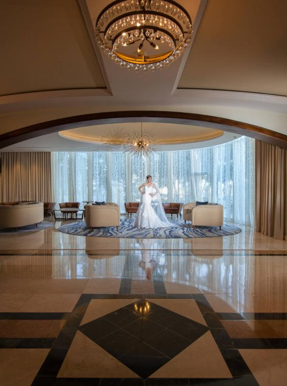 A woman in a wedding dress standing in an opulent hallway.