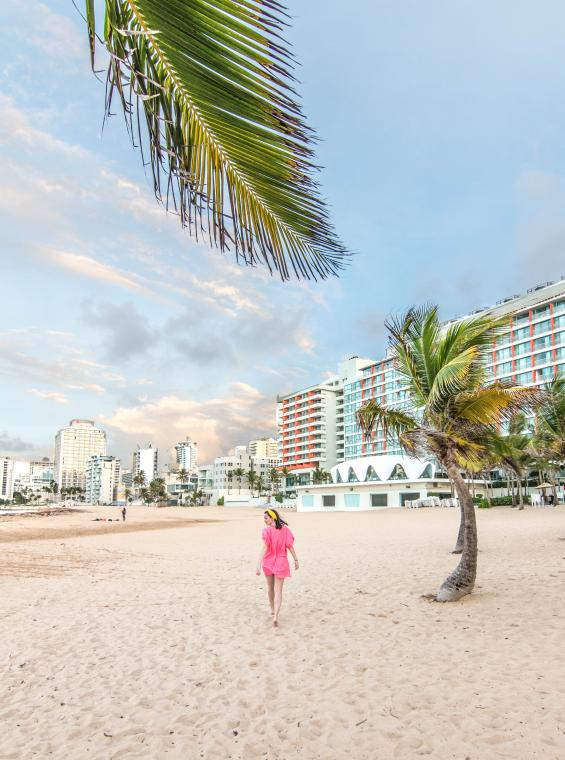 A woman strolls the beach at La Concha Resort in San Juan.